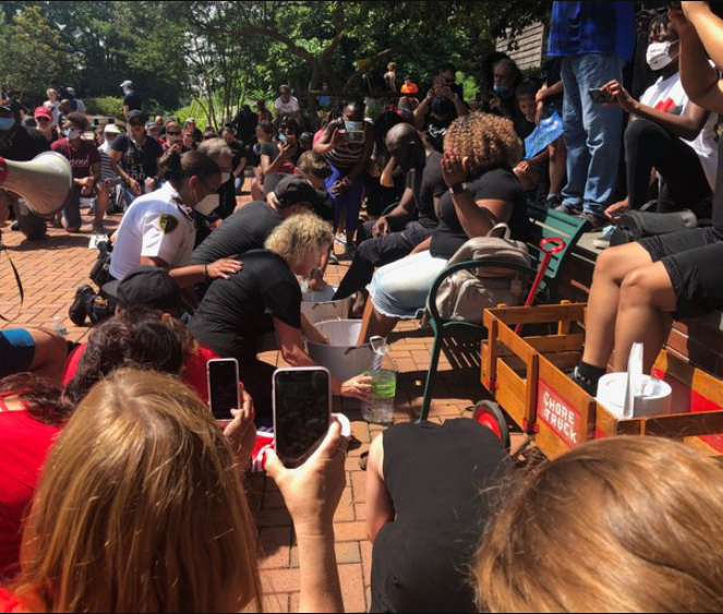 A group of white police officers and other civilians in Cary, North Carolina, came together to wash the feet of black protesters while asking for forgiveness for years of racism.     In a video shared online by Fabiola Doissaint, the white members of the community are seen cleaning the feet of black religious leaders, while a man says a prayer into a megaphone to repent for their sins and historical involvement in slavery and oppression against African-Americans.     The man holding the megaphone, while praying, acknowledged that there's only one race of people. He then asked for forgiveness for their white ancestors enslaving, mistreating and oppressing African-Americans.